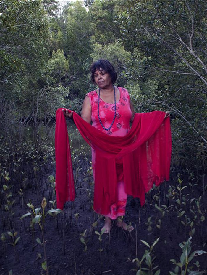 Lois Cook Nyangbul woman stands in the Mangroves of Cabbage Tree island. The red fabric symbolises loss and grief about the history of what happpened to her people. (Catherine Marciniak - Catherine Marciniak)